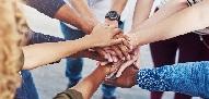 Primer plano de un grupo de personas uniendo sus manos